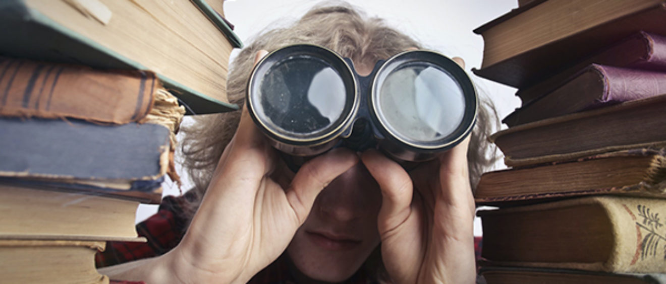 photo of person looking through binoculars between two stacks of books